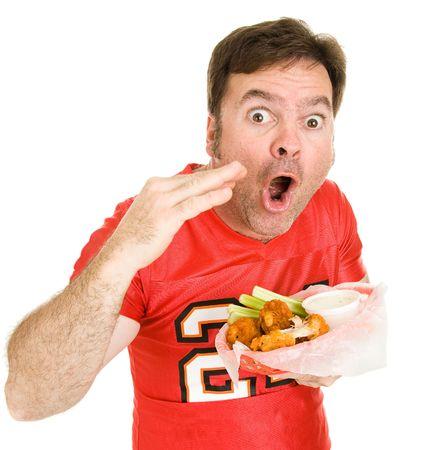 hombre comiendo: F�tbol fan impresionado por su forma de b�falo caliente son alas. Aislado en blanco. Foto de archivo