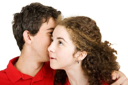 Teen girl listening to a secret whispered by her boyfriend.  Isolated on white.