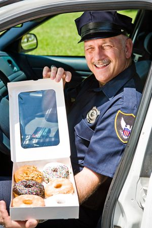 Police officer sitting in his squad car with a box of donuts.   photo