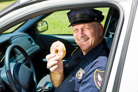 squad: Police officer in his squad car holding a doughnut.   Stock Photo