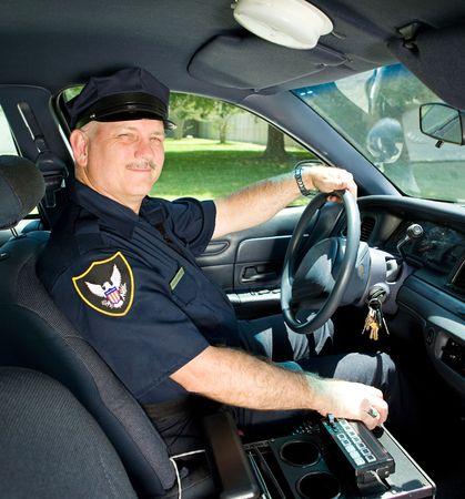 vigilante de seguridad: Apuesto maduro agente de polic�a conduc�a su coche escuadra.  Foto de archivo