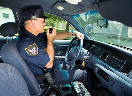 Police officer in his squad car, talking on his radio. Stock Photo - 3611737