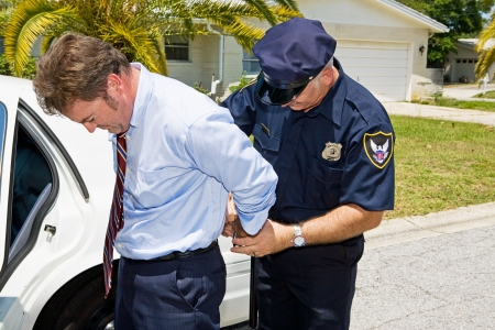 criminal law: Businessman being handcuffed and placed under arrest in front of his home.