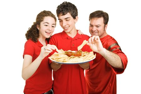 serves: Handsome teen boy serves chips at a football party.  Isolated on white.