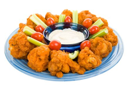 Spicy buffalo wings on platter with celery blue cheese dressing.  Isolated on white.