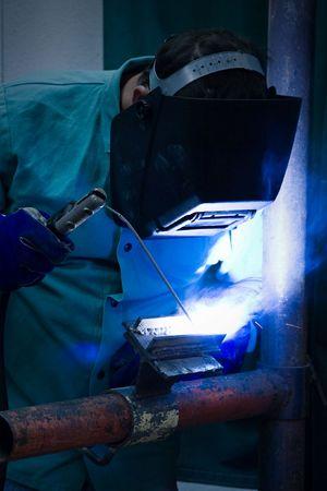 welding metal: Welder working in the blue light of his torch.