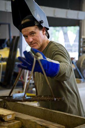 Metal worker in a factory wearing his welding visor.   photo
