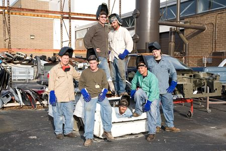 supervisores: Trabajadores de la f�brica de chatarra rodeada de piezas de autom�viles.