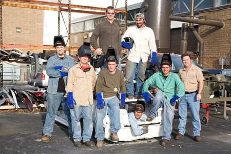 A group of metal workers posing with their supervisor in a scrap metal . photo