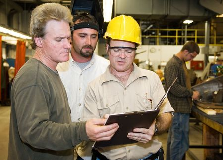 Factory worker and foreman discuss inspection report with auditor.