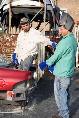 Two metal workers in the scrap metal yard.   photo