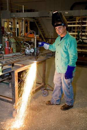Metal worker using a track burner to cut steel with heat.   photo