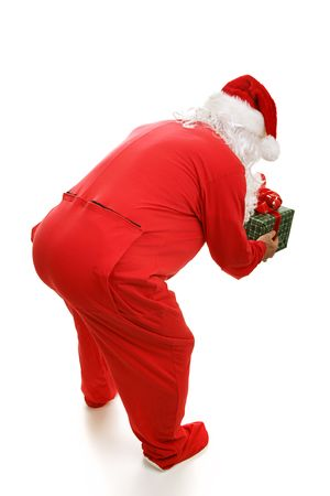 bending over: Santa Claus in footy pajamas, bending over to pick up a present.  Full body isolated on white.