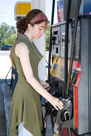 Young woman at the gas station, getting ready to fill up her car.   photo