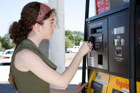 젊은 여자가 그녀의 신용 카드를 사용하여 펌프에서 가솔린 지불합니다.