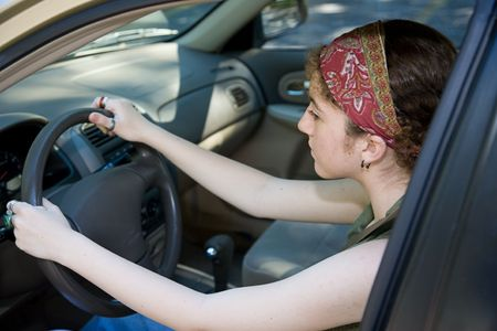 Teen girl concentrates on learning to drive.  Focus on the girls face.   photo