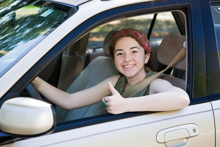 Cute teen driver giving the thumbs up after passing her driving test.   photo