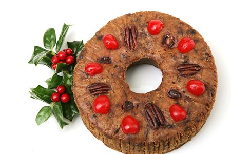 fruitcake: Beautiful Christmas fruitcake topped with cherries and pecans, garnished with colorful holly.  Isolated on white. Stock Photo