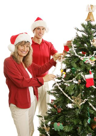 Young adult son helps his mother decorate the Christmas tree.  Isolated on white.   photo