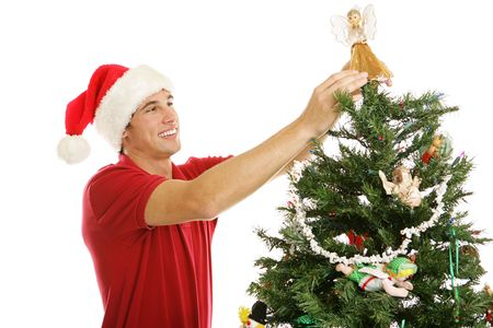Tall handsome young man placing the angel on the top of the tree.  Horizontal view isolated on white.