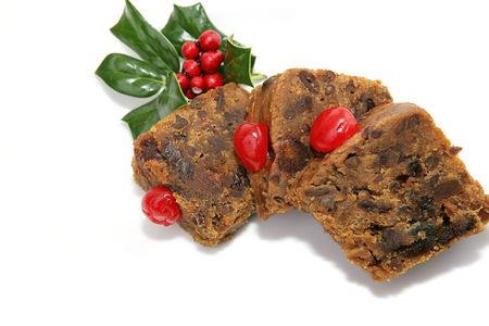Moist delicious Christmas fruitcake slices garnished with cherries and holly.  Isolated on white.