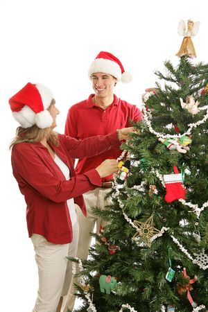 young adult man: Young adult man home for Christmas is helping his mother decorate the tree.  Isolated on white.