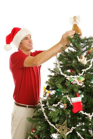 Tall handsome young man placing the angel on the top of the Christmas tree.  Vertical view isolated on white. Stock Photo - 3687313