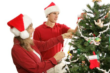 Middle aged mother and her young adult son decorating the Christmas tree together.   photo