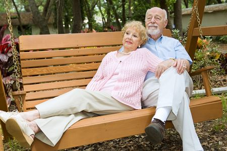 Senior couple taking time to relax together on a park swing.   photo