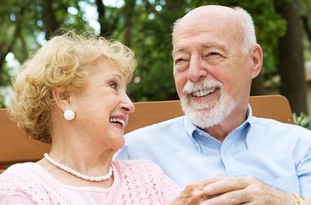 Happy senior couple laughing together.  She is wearing a hearing aid.