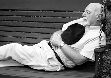 bald man: Black and white image of senior man taking a nap on a park swing.