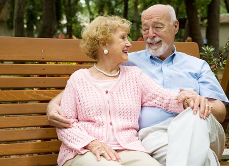 relaxes: Happy senior couple relaxes together on a park bench.