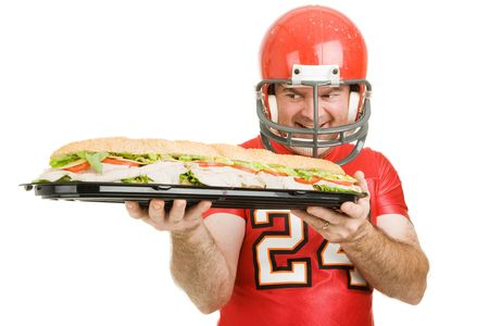 hoagie: Football player hungrily looking at a giant submarine sandwich.  Isolated on white.