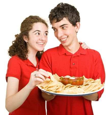 Adorable teen couple snacking on chips and salsa.  Isolated on white. photo