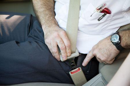 Closeup of a man fastening his seat belt.   photo