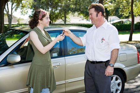 selling: Driving instructor or father handing the car keys to a teen driver.