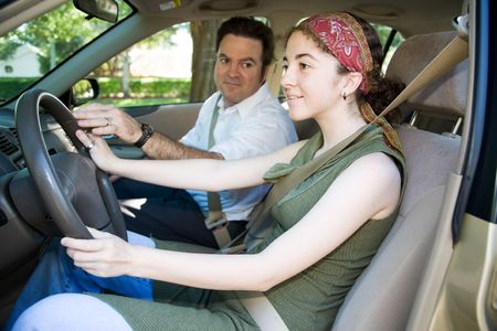 Teen girl taking driving lessons from an instructor or her father.   Foto de archivo