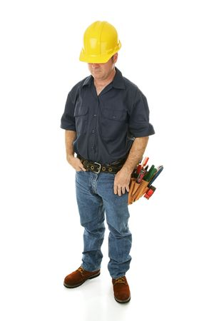 downcast: Depressed, downcast construction worker wondering about his employment prospects.  Isolated.