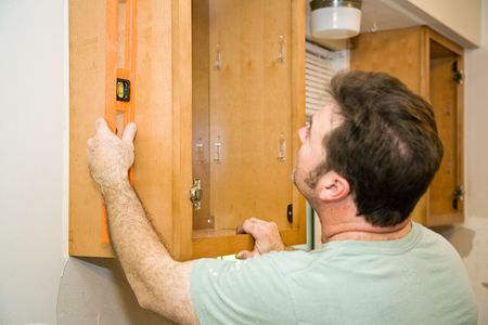 cabinets: Carpenter installing solid maple kitchen cabinets, using a level to check his work.