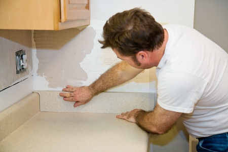 workmanship: Contractor installing a laminate countertop and putting in the back splash.