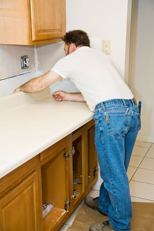 kitchen counter top: Contractor installing a new laminate kitchen counter top.   Stock Photo