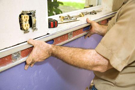 tablaroca: Contratista la instalaci�n de drywall, con un nivel para comprobar su trabajo.