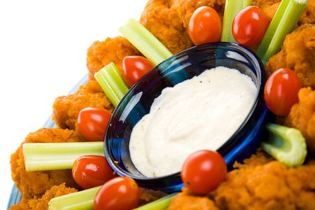 Closeup view of spicy buffalo chicken wings with ranch dressing, celery and grape tomatoes.   Banco de Imagens