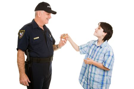 Adolescent boy giving a donut to a police officer.  Isolated on white. photo