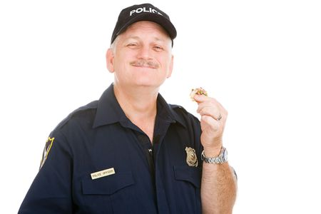 Police officer enjoys finishing off a donut.  Isolated on white.   photo