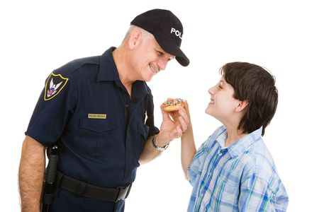 Adolescent boy giving a donut to a friendly police officer.  Isolated on white.   photo