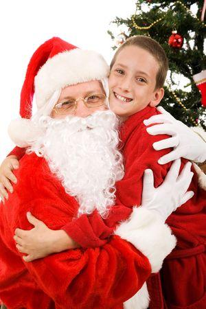 Cute little boy giving Santa Claus a big hug on Christmas morning.   Stock Photo