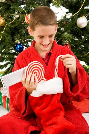 red bathrobe: Adorable little boy opens his stocking on Christmas morning.