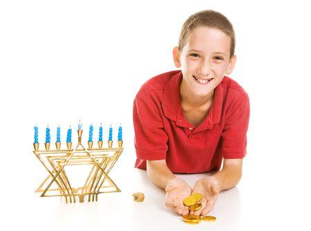 Happy little boy holding Hanukkah gelt he won playing dreidel.  Isolated on white.   photo