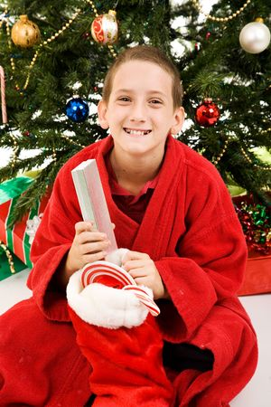 Happy little boy with his stocking on Christmas morning.   Stock Photo